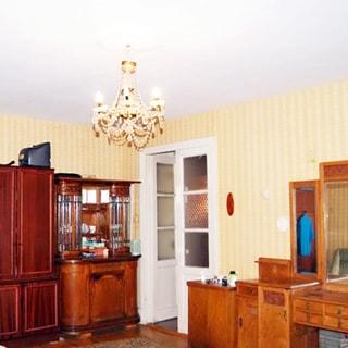 На фото: часть помещения жилой комнаты, двустворчатая дверь в соседнее помещение, слева от двери у стены - комод и шкаф, справа от двери у стены - тумбы и туалетный столик, стены оклеены обоями, на потолке - люстра