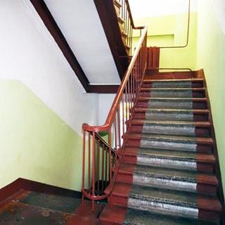 На фото: часть помещения лестничной клетки, металлические перила, на межэтажной площадке - батарея центрального отопления, стены окрашены в пол-высоты, потолок побелен, состояние лестницы - опрятное и чистое