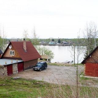 На фото: вид на комплекс с тыльной стороны, на переднем плане - баня с пристроенным гаражом, справа - жилой деревянный одноэтажный дом, между ними - отсыпанная площадка для стоянки автомобилей, на заднем плане - берег реки и река