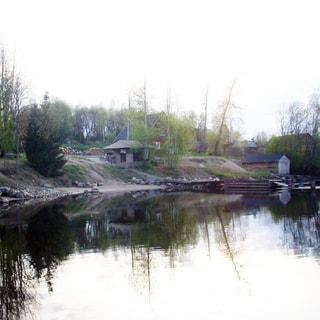 На фото: вид на комплекс с воды, берег с коротким крутым уклоном, каменисто-песчаный, на высокой его части - беседка, на берегу у кромки воды - деревянный эллинг, устроен пирс