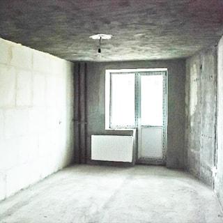 На фото: часть помещения комнаты, одно окно с балконной дверью, стеклопакет, под окном - батарея центрального отопления, стены, потолок и пол выровнены и подготовлены под чистовую отделку