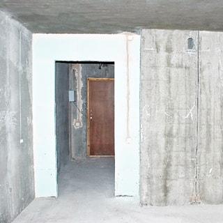 На фото: часть помещения комнаты, дверной проем без заполнения, за проемом видна прихожая и входная дверь в квартиру, стены, потолок и пол выровнены и подготовлены под чистовую отделку