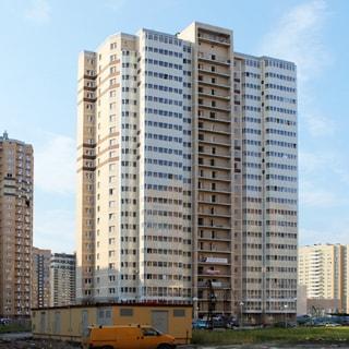 На фото: фасад 23-этажного многоквартирного жилого дома, лоджии застеклены, перед домом - газон и припаркованные автомобили, трансформаторная подстанция, на заднем плане многоэтажная жилая застройка