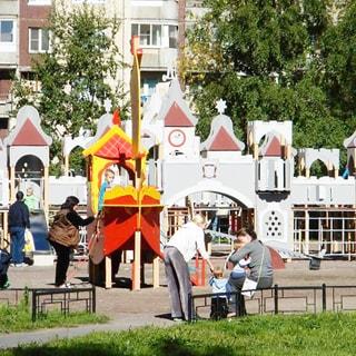 На фото: часть дворовой территории перед домом, благоустроенная оборудованная детская площадка, детский городок, горка, дорожки, газоны, деревья, площадка огорожена