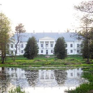 На летнем фото: фасад двухэтажного здания с портиком и колоннами, скатная кровля, перед домом большой земельный участок, трава, деревья, на переднем плане водная гладь пруда