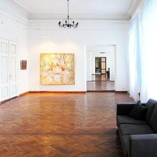 На фото: часть внутреннего помещения дома - просторный зал музейного типа, на стенах - картины, из мебели один диван справа у стены, по правой стене окна, полы - паркет, стены окрашены, на потолке люстра и точечные светильники