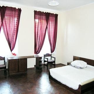 На фото: часть помещения гостиничного типа, два окна, двуспальная кровать, небольшой письменный стол, два стула, полы - паркет, стены - окрашены, на потолке - люстра