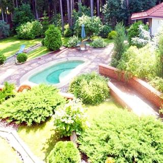 На фото: вид из окна на территорию придомового участка, выполнен ландшафтный дизайн, дорожки вымощены камнем, разбиты газоны, высажены декоративные садовые растения, устроен пруд