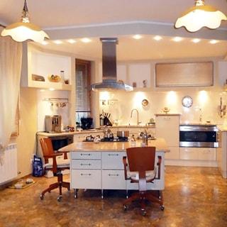 На фото: часть внутреннего помещения дома - кухни-столовой, посреди комнаты широкая тумба-стол с обеденной частью и варочной поверхностью, над варочной поверхностью - вытяжка, у стола - два стула на колесиках, прямо у дальней стены - кухонный гарнитур со встроенной кухонной техникой, полы - облицованы камнем, на потолке - две люстры
