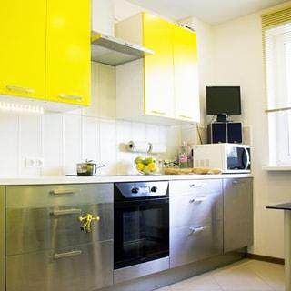 На фото: часть помещения кухни, справа - окно, слева от окна вдоль стены - кухонный гарнитур, столы-тумбы с металлизированными фасадами, навесные шкафы, кухонная плита с духовым шкафом, над ней - вытяжка, полы - плитка
