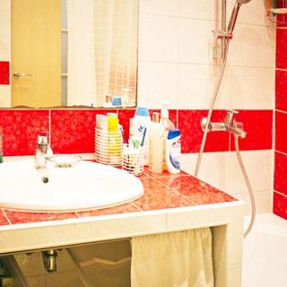 На фото: часть помещения ванной комнаты, керамическая раковина со смесителем вмонтирована в столешницу, облицованную плиткой, над ней - зеркало, справа ванная со смесителем для ванной, стены облицованы керамической плиткой