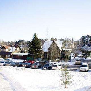На фото: зимний вид из окна на придомовую территорию, дорожки очищены от снега, на проезжей части припаркованы автомобили, на дальнем пане - малоэтажная частная жилая застройка