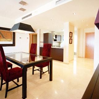 На фото: часть помещения жилой комнаты - гостиной, посредине комнаты - стол со стеклянной столешницей, вокруг стола - четыре стула, над столом - люстра, полы - плитка, на дальнем плане справа - через арку видна часть помещения кухни