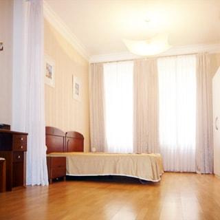 На фото: часть помещения жилой комнаты - спальни, два окна, слева у стены - двуспальная кровать с деревянными подголовниками, левее - прикроватная тумбочка и туалетный столик, напротив кровати у противоположной стены - одежный шкаф, полы - ламинат, на потолке - люстра
