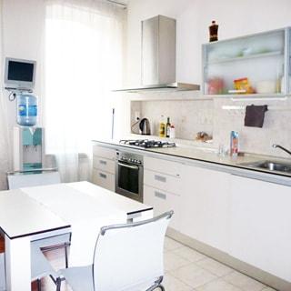 На фото: часть помещения кухни, два окна, между окон на стене - небольшая телевизионная панель, под ней - кулер с водой, у правой стены от самого окна - кухонный гарнитур с общей столешницей, четырехкомфорочная газовая плита, над ней - вытяжка, правее - навесные кухонные шкафы, металлическая мойка со смесителем, посредине комнаты - обеденный стол со стульями, полы - плитка