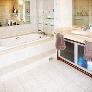 На фото: часть помещения ванной комнаты, прямо у стены - ванная, вмонтированная в основание, смеситель, зеркало, полки, справа у стены - раковина на широкой тумбе со столешницей, стены и полы облицованы плиткой