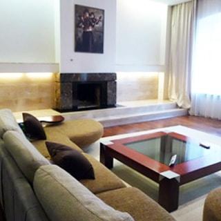 На фото: часть помещения жилой комнаты - гостиной, справа - окно, прямо у стены - небольшой подиум и камин, над камином - картина, перед ним - мягкий диван, перед ним - журнальный столик, полы - ламинат, на полу - ковер