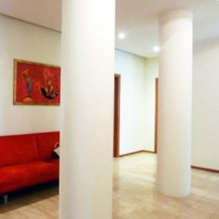 На фото: часть помещения прихожей, в центре две колонны, прямо у стены за колоннами - диван, над ним - эстамп, правее - двери в соседние помещения, полы - ламинат, стены и потолок окрашены, на потолке - точечные светильники