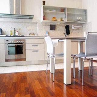 На фото: часть помещения кухни, прямо у стены - кухонный гарнитур с общей столешницей, плита с духовым шкафом, над ней - вытяжка, правее - навесные кухонные шкафы, под ними - мойка со смесителем, посредине комнаты - обеденный стол со стульями, полы - плитка, ламинат