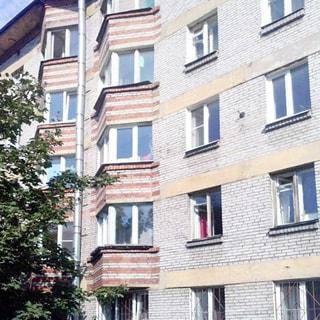 На фото: часть фасада пятиэтажного кирпичного многоквартирного жилого дома, эркеры, балконов нет, у дома - деревья