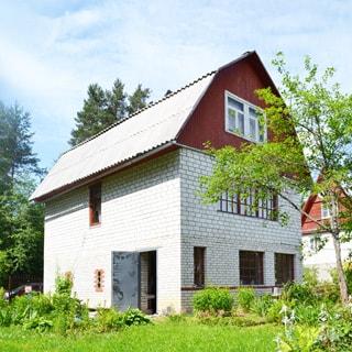 На фото: кирпично-блочный двухэтажный одноквартирный дом с мансардй, кровля скатная ломаная, покрытие - шифер, на придомовом участке - газон, грядки, клумбы, садовые посадки и деревья