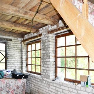 На фото: часть внутреннего помещения дома, без внутренней отделки, межэтажное перекрыте - доски по деревянным балкам, в окнах одинарные верандные рамы, на переднем плане справа - деревянная лестница на верхний этаж