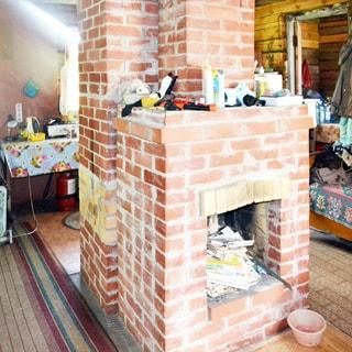 На фото: часть внутреннего помещения дома, посредине комнаты - кирпичный камин с кирпичным дымоходом, за камином - окно, справа у стены - кровать, полы - линолеум, постелена ковровая дорожка