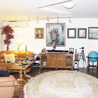 На фото: часть помещения жилой комнаты - гостиной, слева в углу мягкий диван угловой, перед ним - журнальный столик, правее у стены - четырехсекционная тумба, на стенах эстампы, кондиционер, полы - ламинат, на полу - круглый ковер, на потолке - точечные светильники