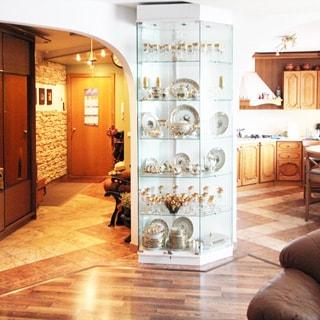 На фото: часть открытого пространства из нескольких помещений - прихожей, комнаты, кухни, в прихожей - одежный шкаф, полы - плитка, в комнате полы - ламинат, в кухне - встроенная кухонная мебель и техника, обеденный стол, полы - плитка, между кухней и прихожей - стеклянный стеллаж с посудой