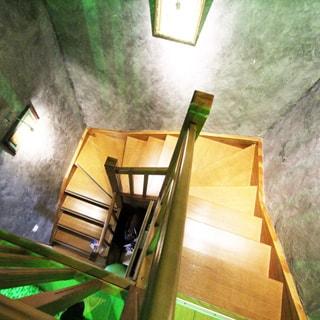 На фото: вид на лестницу и лестничный пролет с высоты площадки второго уровня, три пролета по 5-6 ступенек по периметру лестничного пролета, перила и ступеньки деревянные, на стенах пролета - светильники