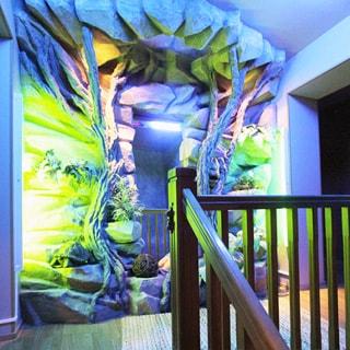 На фото: вид на лестничную площадку второго уровня с верхних ступенек лестницы, площадка огорожена деревянными перилами, на стене площадки выполнена инсталляция в желто-зеленых и синих тонах, справа - арка прохода в помещения второго уровня