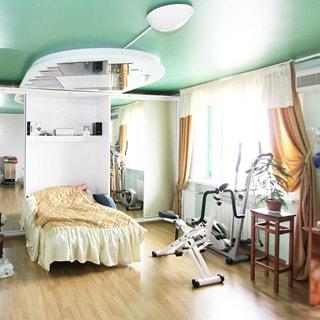 На фото: помещение жилой комнаты, справа - окно, у окна на стене - кондиционер, слева от окна вдоль всей стены секционный шкаф, в том числе секция с кроватью в положении разложена, рядом с кроватью - два спортивных тренажера, полы - ламинат, потолок окрашен,  на потолке - люстра, над кроватью - зеркало на потолке