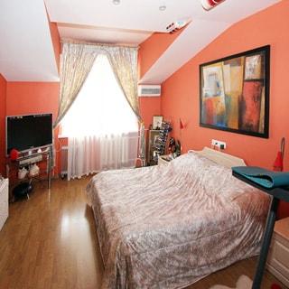 На фото: часть помещения жилой комнаты - спальни, одно окно, слева от окна - тумба с телевизионной панелью на ней, левее вдоль стены - тумба и комод, справа у стены - двуспальная кровать, стены и потолок окрашены, полы - ламинат, потолок разновысотный мансардного типа. на потолке - точечные светильники