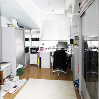 На фото: часть помещения жилой комнаты, одно окно, потолок разновысотный мансардного типа, прямо у окна - письменный стол, у стола - офисное кресло, слева и справа - тумбочки, слева у стены - шкаф, справа у стены - комод и шкаф, на столе и на полках - оргтехника, полы - ламинат, стены и потолок окрашены в белый цвет, на стене - кондиционер
