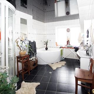 На фото: часть помещения ванной комнаты, одно окно, слева от окна угловая ванная, справа от окна у стены - керамическая раковина на тумбе, полы и стены облицованы плиткой, полы - темной, стены - белой
