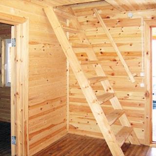 На фото: часть внутреннего помещения дома, входная дверь на улицу и дверь в соседнее помещение открыты, деревянная лестница в мансардный этаж, полы - дощатые, стены и потолок обшиты вагонкой