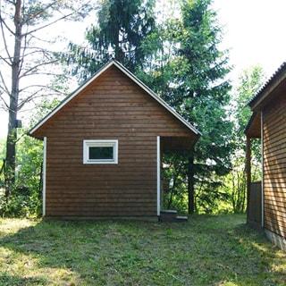 На фото: придомовая территория участка, справа - стена дома, прямо - деревянная баня с крыльцом, участок покрыт травой, за баней - деревья
