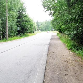 На фото: автомобильная асфальтированная дорога, двухполосная, с обочинами, справа и слева - кустарник и деревья, впереди на дальнем плане - автобусная остановка