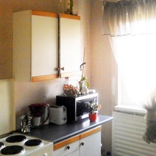 На фото: часть помещения кухни, одно окно, слева от окна вдоль стены - кухонный стол-тумба, на столе - микроволновая печь, тостер, над столом - навесной шкаф, слева от стола - четырехкомфорочная электроплита