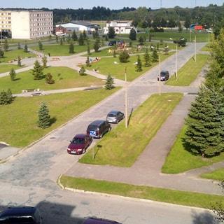 На фото: вид из окна на придомовую территорию, пешеходные дорожки и внутриквартальные проезды асфальтированы, припаркованы автомобили, разбиты газоны, высажены деревья, устроены детская площадка, вдоль дорожек размещены садовые скамейки