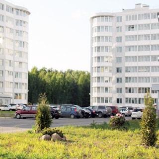 На фото: благоустроенная придомовая территория с газоном и местом для парковки автотранспорта, на заднем плане - часть фасадов двух одинаковых девятиэтажных многоквартирных жилых домов, балконы и лождии застеклены