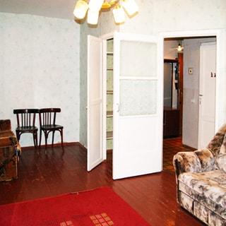 На фото: часть помещения жилой комнаты, дверь в коридор открыта, справа от двери у стены - мягкий диван-кровать, слева от двери - встроенный шкаф-кладовка, левее у стены - два стула и кресло, стены оклеены обоями, на потолке - люстра, полы - крашеная доска, на полу - ковер