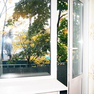 На фото: балконный блок - дверь и одностворчатое окно, стеклопакет, дверь на балкон приоткрыта, балкон не остеклен, за балконом на улице - деревья