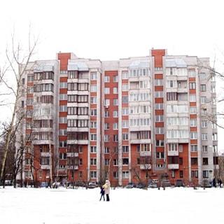 На зимнем фото: фасад девятиэтажного отдельно стоящего кирпичного многоквартирного жилого дома со стороны сквера, по фасаду - балконы, частично застеклены, перед домом припаркованные автомобили, на переднем плане - огороженная забором парковая зона, деревья, кустарники
