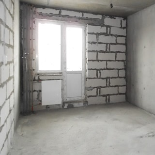 На фото: часть помещения комнаты без отделки, одно окно, установлен стеклопакет, полы - цементно-песчаная стяжка, электророзетки установлены, радиатор батареи центрального отопления отсутствует