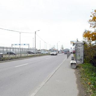 На фото: проезжая часть, тротуар, автобусная остановка павильонного типа, уличная скамья, за тротуаром - газон, кусты, на противоположной стороне за проезжей частью - огороженная площадка для стоянки автотранспорта с находящимися на ней автомобилями