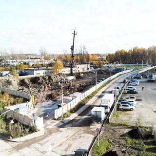 На фото: огороженная бетонным забором строительная площадка нулевого цикла, идет выборка грунта и забивка свай, прилегающая проезжая часть и тротуары - асфальтированы, на соседнем участке - стоянка автомобилей