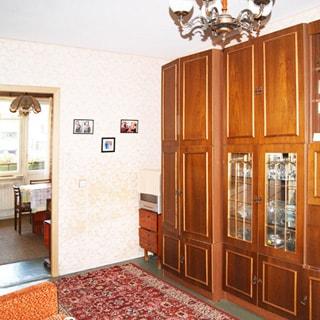 На фото: часть жилой комнаты, вдоль стены - мебельный гарнитур (шкафы, сервант, полки, тумбы), стены оклеены обоями, на потолке - люстра, на полу - ковер, дверь в соседнюю комнату, в соседней комнате - окно, у окна - стол, у стола - стулья, на потолке - люстра