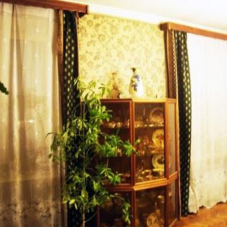 На фото: часть помещения жилой комнаты, два окна, между окнами у стены - трехстворчатый шкаф со стеклянными дверями с посудой, на шкафу - ваза, рядом со шкафом - декоративное растение, стены оклеены обоями, полы - паркет