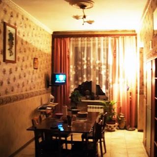 На фото: часть помещения жилой комнаты, одно окно, слева от окна на стене на кронштейне - небольшой телевизор, слева у стены - обеденный стол со стульями, справа у стены - шкафы, стены оклеены обоями, полы - керамическая плитка, на потолке - люстра